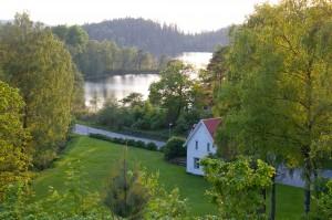 Somrig flygbild på folkhögskolan med gröna träd och sjön i bakgrunden